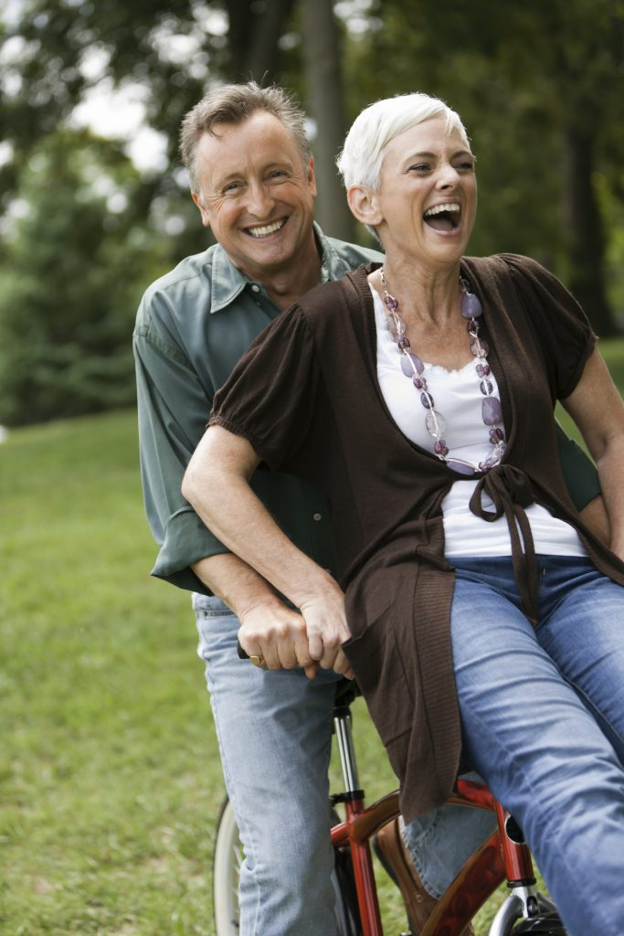Older couple having fun on a bicycle