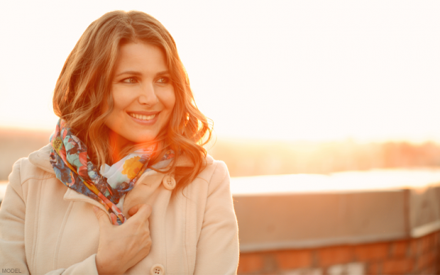 Woman in a Fall coat in front of a sunset